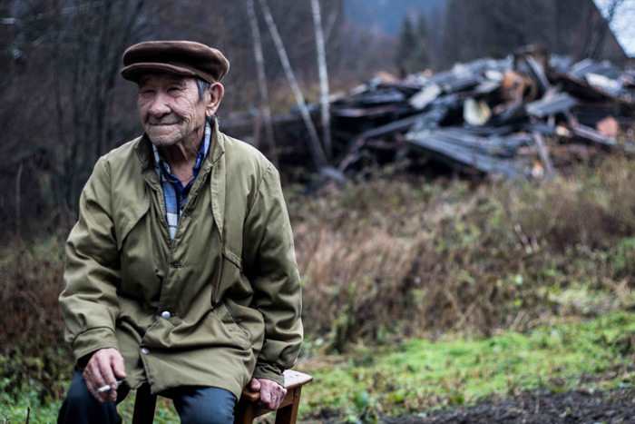 A villager in Kazas sitting by his burned out house. Credit RAIPON
